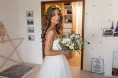 Wedding flowers in bride hands in interior bride in a designer d Stock Photos