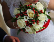 Wedding flowers. Bright festive wedding bouquet in hands of the bride royalty free stock images