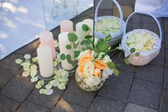 Wedding Flowers and Candles Decoration. Wedding reception centerpiece close-up with pastel orange and white Stock Photos