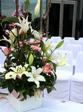 Wedding flowers and chairs. Wedding flowers and linen covered chairs Royalty Free Stock Image