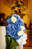 Wedding flowers in a church. At the end of a pew Royalty Free Stock Image