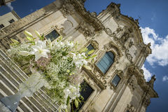 Wedding flowers and church. White wedding flowers as decoration in front of church Royalty Free Stock Photos