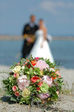 Wedding flowers and couple. Focus on the bouquet. Bouquet, bride and groom Stock Photos