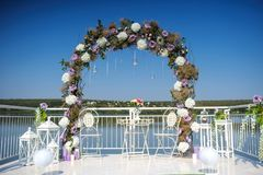 Wedding flowers decoration from ranunculus and roses. Beautiful arch for reception on the lake Stock Photo