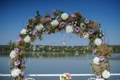 Wedding flowers decoration from ranunculus and roses. Beautiful arch for reception on the lake Stock Photos