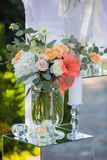 Wedding Flowers Decoration. Wedding reception centerpiece close-up with pastel orange and white Royalty Free Stock Photography