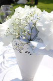 Wedding Flowers. Delicate white wedding flowers with babies breath on the inside. The vase is a white lace pattern. In the distance, is a champagne glass and on Stock Photos