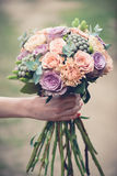 Wedding flowers. Flower bouquet in hand, bride holding floral bouquet. Mixed flowers, rose, gerber Stock Image