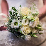 Wedding flowers, girl bride holding bouquet of white flowers and white yellow milk roses. Bouquet of roses, bridal bouquet, bride morning, wedding gown Stock Image