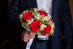 Wedding flowers. Groom holds bouquet of white flowers and red roses, bouquet of roses, bridal bouquet, groom's fees Stock Images