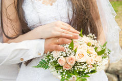 Wedding flowers. Hands of newlyweds with rings, against a wedding bouquet Stock Photo