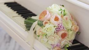 Wedding flowers lie on the keys of the piano. She takes the bouquet stock video footage