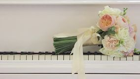 Wedding flowers lie on the keys of the piano. stock footage