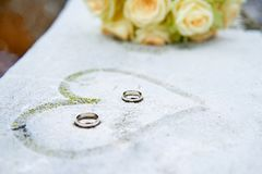 Wedding flowers, rings and painted heart on frozen surface Royalty Free Stock Photos