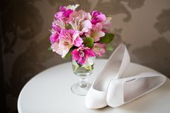 Wedding flowers and shoes. Wedding bouquet and white bride shoes stock image