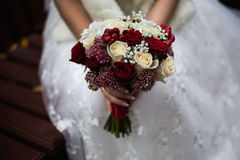 Wedding flowers, wedding bouquet, the bride holding a bouque. T of red and peach, dairy roses and white flowers, wedding ceremony Stock Photo