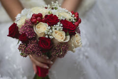 Wedding flowers, wedding bouquet, the bride holding a bouquet of red and peach, dairy roses. And white flowers, wedding ceremony Royalty Free Stock Photography