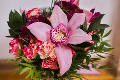 Wedding flowers, wedding bouquet of red and pink peach yellow roses and blue violet purple orchid. Bouquet of blue, purple, purple flowers, roses, orchids stock images