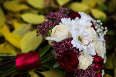 Wedding flowers, wedding rings lie on a wedding bouquet, bouquet of red and peach, dairy roses and white flowers Stock Photos