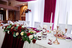 Wedding flowers of white and red roses on table of newlyweds. Stock Image