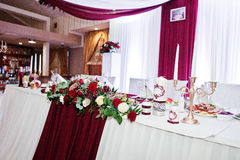 Wedding flowers of white and red roses on table of newlyweds. Stock Photo