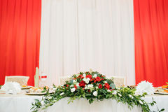 Wedding flowers of white and red roses on table of newlyweds. Stock Images
