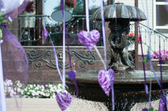 Wedding fountain. The fountain with angels and wedding jewelry in the form of violet hearts and ribbons Stock Photos