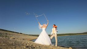 Wedding Fun. Bride and groom making soap bubbles on a lake stock footage