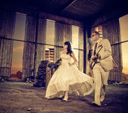 Wedding gangs. Wedding couple with guns running at industrial place Royalty Free Stock Photos