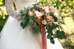 Wedding gentle disheveled bouquet of peach shades with pink ribbon. Horizontal photo, side view Stock Photos