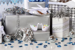 Wedding Gifts. Silver and blue-wrapped wedding (or silver anniversary) gifts decorated with two tiny candy-holding swans, mirrow balls and scattered glass Royalty Free Stock Image