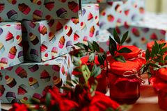 Wedding gifts for guests: boxes with cakes, sweet jars with jam and pouches with candies. Presents and bonbonnieres in red colors. Decorated with greenery Stock Photo