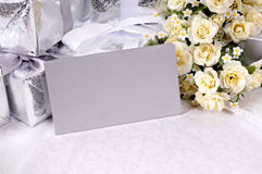 Wedding invitation background envelope white copy space. Silver gray envelopes or invitations with several wedding gifts and white rose bouquet laid on bridal Stock Images