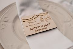 The wedding gifts to the guests. The wooden magnet on the white plate royalty free stock photos