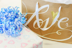Wedding Gifts. A wrapped wedding gift with hearts and blue curling ribbon and a gift bag with the word Love on it stock photography