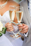 Wedding glasses. Bride and groom holding wedding heart-shaped glasses with champagne Royalty Free Stock Photos