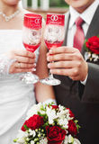 Wedding glasses. Bride and groom holding beautifully decorated wedding glasses with champaign Royalty Free Stock Images