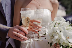 Wedding glasses. Bride and groom holding beautifully decorated wedding glasses with champaign Stock Photography