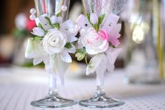 Wedding glasses. Beautiful wedding glasses decorated with artificial flowers on the festive table closeup Royalty Free Stock Photo