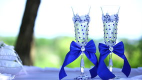 Wedding glasses with blue bows. Wedding glasses with blue ribbons on a white tablecloth stock video footage