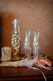 Wedding glasses and a bottle of white roses with decor Royalty Free Stock Images
