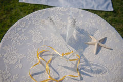 Wedding glasses and rings on the shells and starfish. Table with lace cover. Stock Photography