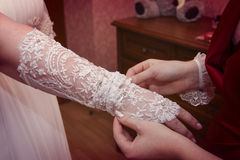 Wedding glove. A young women helps to wear a white lace glove Stock Photo