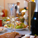 Wedding goblet. On festive decorated table is adorned wine glasses and a bottle of champagne Stock Photography
