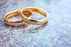 Wedding gold diamond rings on gray background Stock Photo