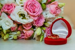 Wedding gold ring. Romantic engagement two diamond rings are in a red box in the shape of a heart, they lie near a stock images