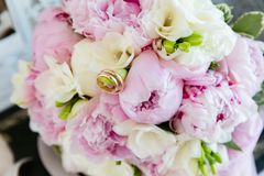 Wedding gold rings on a bouquet of flowers stock photo