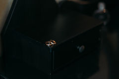 Wedding gold rings on a decorative black box, lie on the table. Jewelry concept Royalty Free Stock Photos