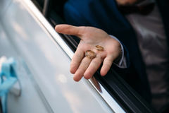 Wedding gold rings lie on the hand of groom. Jewelry concept Royalty Free Stock Images