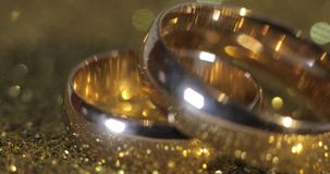 Wedding gols rings lying on shiny glossy surface. Shining with light. Close-up. Wedding gold rings lying on shiny glossy surface. Shining with light. Close-up stock video